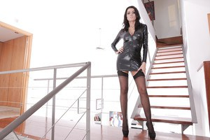 Brunette solo girl Ania Kinski freeing big tits from latex dress in stockings