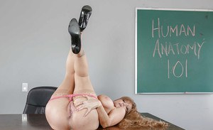 Mature pornstar Darla Crane exposing big tits in tan nylons on teacher's desk