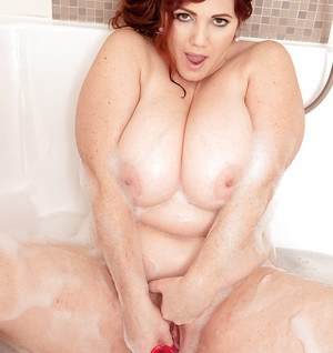Redhead fatthy Roxee Robinson enjoys a soapy solo with a sex toy in a bath