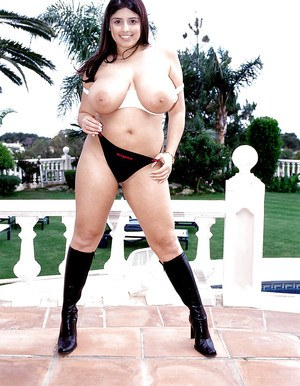 Fat MILF Kerry Marie inserting sex toy in twat on patio in black boots