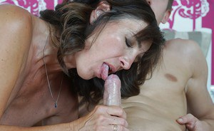 Naked grandma Mariana giving a young man blowjob on her bed