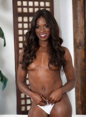 Ebony pornstar Ana Foxxx removing panties before slathering oil on nude body