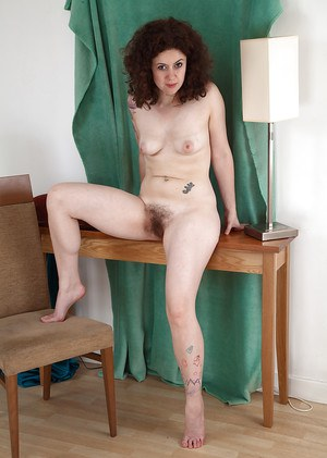 Mature woman with curly hair opens her nice legs to boast of her hairy holes