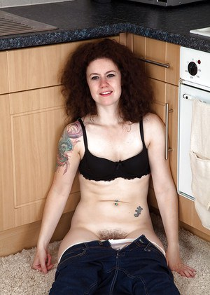 Mature brunette woman Candy revealing hairy snatch while disrobing in kitchen