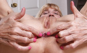 Leggy granny Bossy Ryder stretching cunt lips wide open after undressing