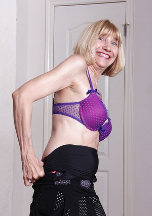Leggy grandma Bossy Ryder undressing to display trimmed bush