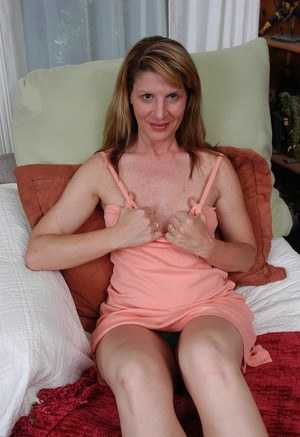 Mature lady Linda tugging on labia lips after getting naked on bed