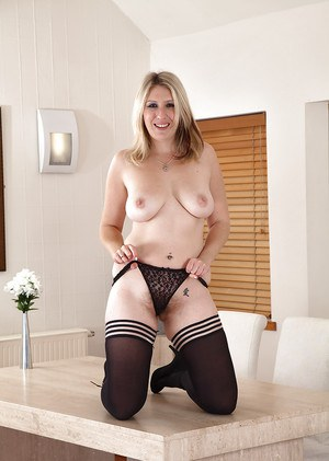 Mature lady Mel Harper showing off hairy cunt in stockings and pumps