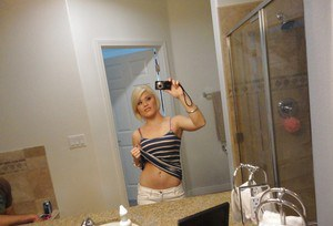 Young blonde hottie Ash Hollywood taking selfies in mirror while undressing
