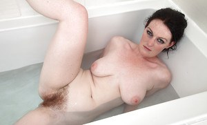 Mature solo model Andrea Foster freeing hairy cunt from wet panties inbathtub