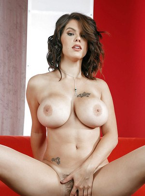 Brunette pornstar Peta Jensen showing off big fake tits while undressing