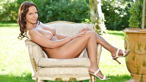 Euro model Eve displaying perfect nude body outdoors on grassy lawn