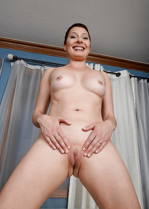 Barefoot mature lady Kali Karinena showing off bald cunt after panty removal