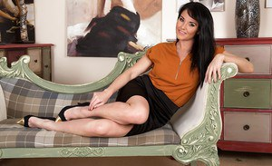 Brunette MILF Danielle Leah Raven stripping off clothes on chesterfield