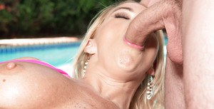 Mature blonde lady Savannah Steele sucking cock beside swimming pool