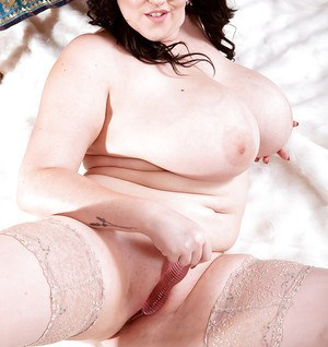 Brunette BBW Lila Payne flaunting massive tits on bed in stockings and heels