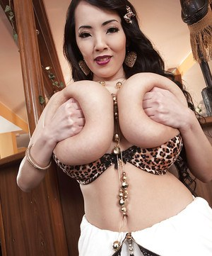 Asian beauty Hitomi unleashing massive tits wearing black nylons