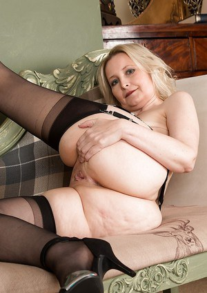 Older blonde dame Emma Turner stripping down to mesh garters and stockings