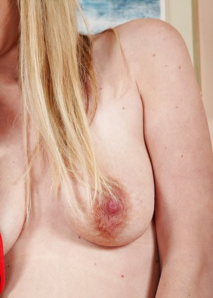 Aged blond woman Ashleigh McKenzie modeling in the nude after doffing lingerie