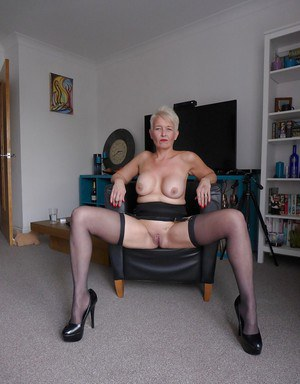 Aged blond lady Scarla Swallows displaying bald pussy in stockings and garters