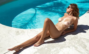 Busty centerfold model Ali Rose posing next to pool in sunglasses