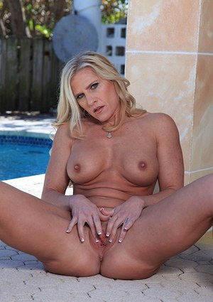 Gorgeous mature vixen with big fake tits spreads legs to rub her adorable cunt
