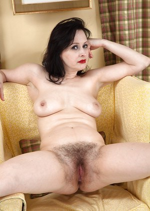 Mature brunette lady Nikita getting naked to show off her hairy natural pussy