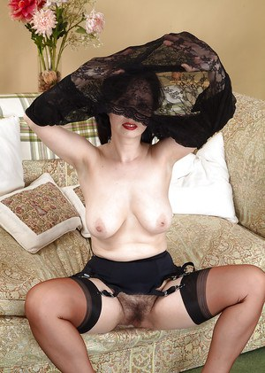 Mature dame Nikita stretching her hairy pussy in black nylons and garters