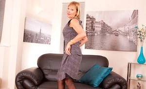 Mature woman Elaine stripping down to black stockings and garters on couch