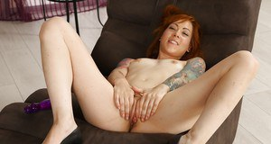 Heavily inked redhead Foxie T toying her wet pussy with a purple sex toy
