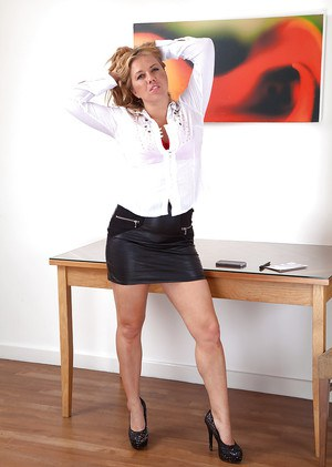 Mature woman Elle Macqueen slips off skirt and panties to demonstrate beaver