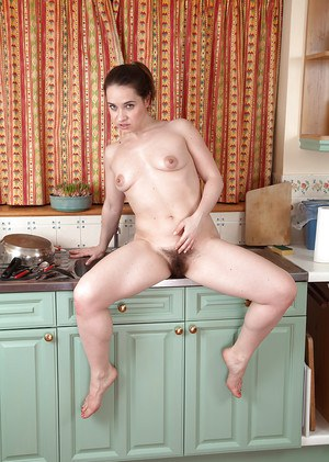 European babe in jeans strips off in the kitchen and squats showing hairy cunt