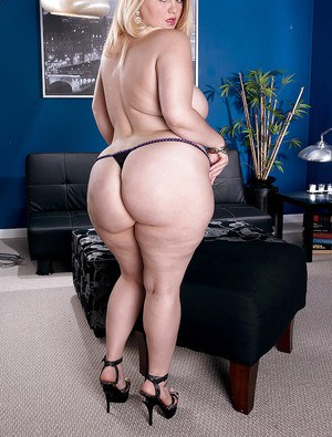 Fat blonde female Mazzaratie Monica unveiling massive ass on leather sofa