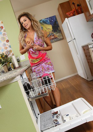 Older woman Elli Taylor taking off dress and panties to pose nude in kitchen