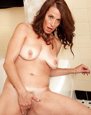 Middle aged lady Mimi Moore undressing before playing with herself in bathtub