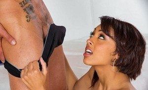 Hot ebony chick Cherry Hilson stands on her knees and sucks a massive pecker