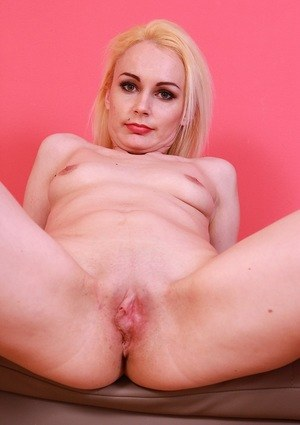Young Roxy Lee stands naked with the lesg wide open to pose her pink puss