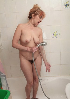 Mature Karolina loves pouring warm water on her furry pussy and big tits