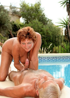 Naked older redhead Eve gives a BJ beside pool for her first time experience