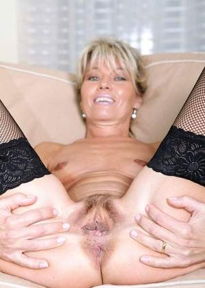 Elegant mature pornstar in stockings shows trimmed pussy in a closeup shoot