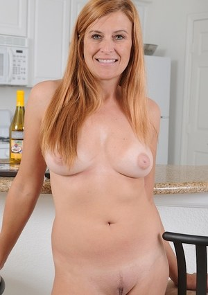 Aged lady with red hair Anita Coxxx showcases her moist pussy on kitchen stool