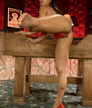 Older Asian Max Mikita crosses and uncrosses her bare legs on roulette table