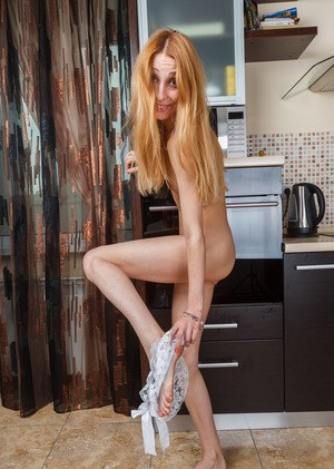 Pale older redhead Kler slides jeans and sexy panties over her long legs