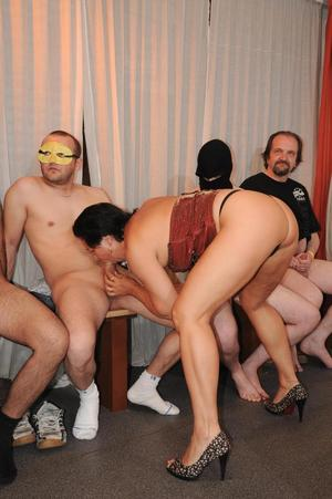An older woman sucks and fucks a roomful of men during hard gangbang action