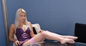 European MILF Brandy Smile poses in sexy purple lingerie and pink stockings