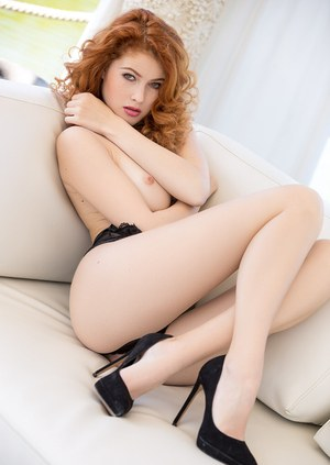 Beautiful redhead Heidi Romanova poses naked on sofa for centerfold spread