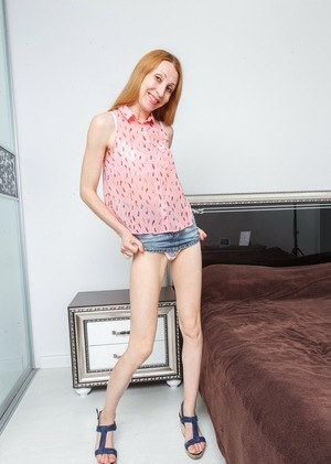 Skinny mature redhead with long legs and medium-sized tits shows a hairy twat