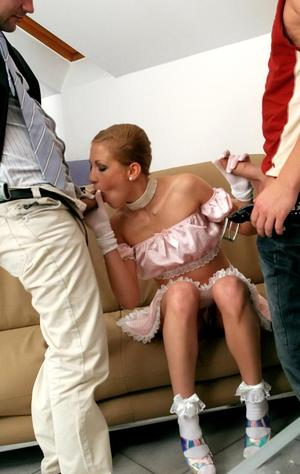 Fully clothed maid sits on a sofa while servicing two cocks at the same time