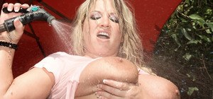 Middle-aged blonde Rachel Love wets her hooters with garden hose in yard