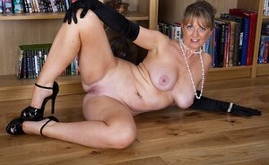 Classy mature woman Sophie plays with her pink pussy in long black gloves